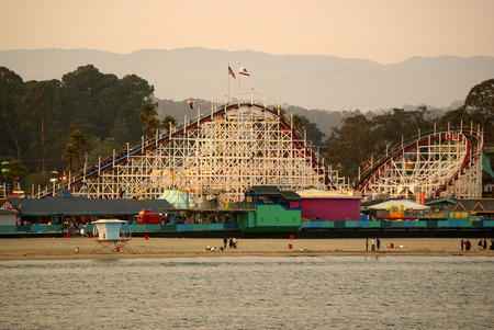 Santa Cruz Bay area in California, USA, thronged by visitors with parked boats and ships, majestic buildings, rows of palms and play areas.