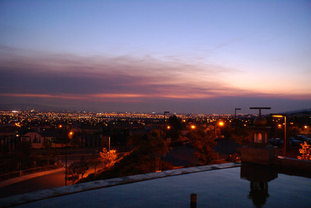 View of San Jose city just after sunset, California from near Sikh Gurdwara on hill, with golden sky and haze just above the horizon, city lights.