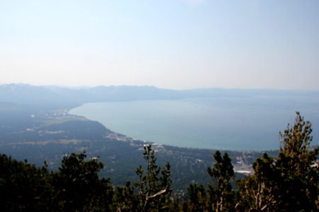 View of Lake Tahoe, buildings and shoreline from upper deck of Heavenly Gondola, providing panoramic view of low isolated clouds and distant mountain ranges.
