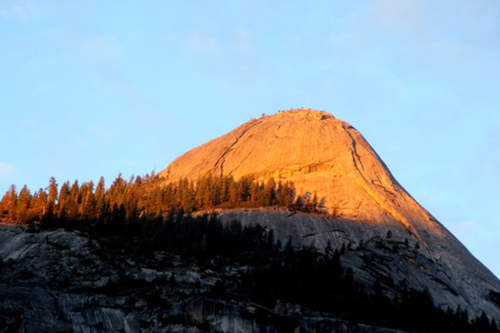 Sunset on North Dome, Yosemite, view from Curry Village Parking, intense orange Yellow color rays at 16.47, November 24, on upper half of the dome slowly changing to orange and finally red Foto de archivo