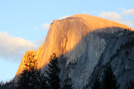 Sunset on Half Dome, Yosemite, view from Curry Village Parking,  orange yellow color rays at 16.45, November 24, on upper half of the dome slowly changing to finally red Editorial