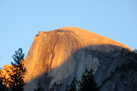 Sunset on Half Dome, Yosemite, view from Curry Village Parking, darker orange yellow color rays at 16.46, November 24, on upper half of the dome slowly changing to finally red
