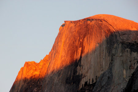 Sunset on Half Dome, Yosemite, view from Curry Village Parking, intense orange red color rays at 16.52, November 24, on upper half of the dome slowly changing to finally red Foto de archivo