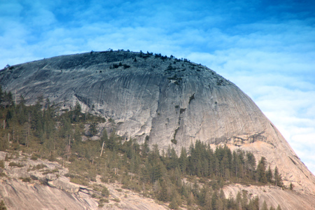 Evening view of North Dome, Yosemite National Park, California, zoomed in view from Curry Village just after the last rays of Sun left the peaks, a granite rock, southernmost summit of Indian Ridge. Stock Photo