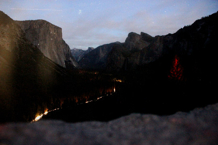 Early night view of peaks from Tunnel view, Yosemite National Park, California, with traffic lights, camping sites and mountaineers climbing on rocks mainly El Capitan on left.