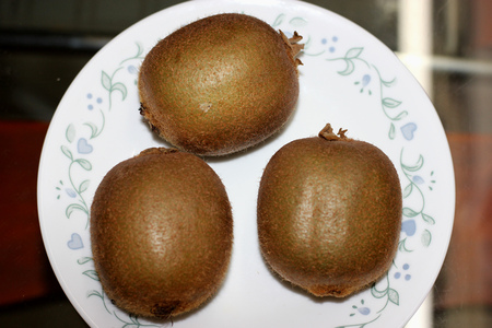 Fuzzy kiwifruit or mangüeyo, Actinidia deliciosa, popular fruit from china with oblong dark brown fuzzy fruits and greenish pulp and minute black seeds.