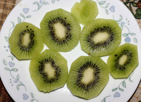 Section of Fuzzy kiwifruit or mangüeyo, Actinidia deliciosa, popular fruit from china with oblong dark brown fuzzy fruits and greenish pulp and minute black seeds.