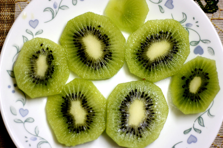 Section of Fuzzy kiwifruit or mangüeyo, Actinidia deliciosa, popular fruit from china with oblong dark brown fuzzy fruits and greenish pulp and minute black seeds. Stock Photo