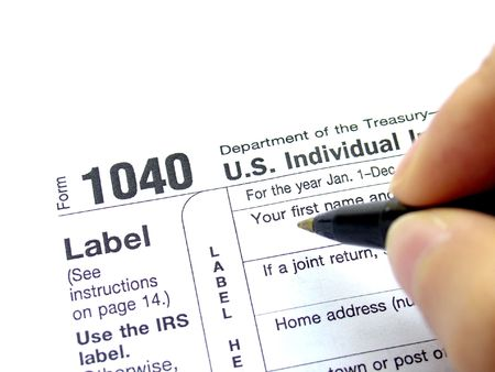 Filling federal tax forms with a pen Stock Photo - 4963729