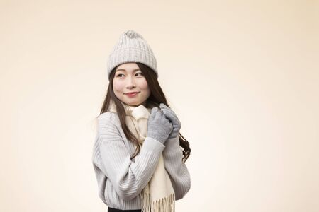 Portrait of young woman wearing winter clothes against beige background