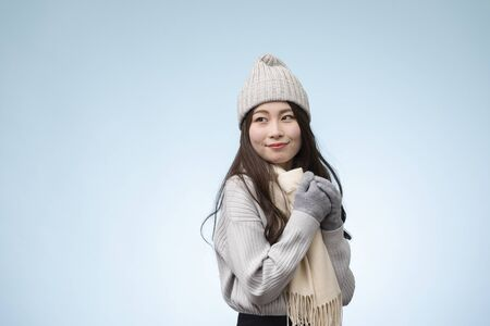 Portrait of young woman wearing winter clothes against light blue background
