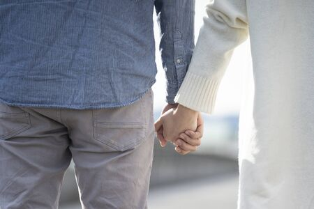 Hands of a young couple holding hands