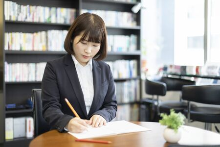 Woman sitting at desk and working 写真素材