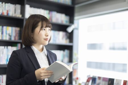 Woman reading a book in front of a bookshelf
