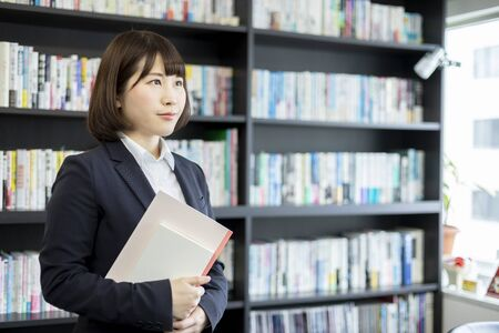 Woman holding a book and notebook in front of a bookshelf