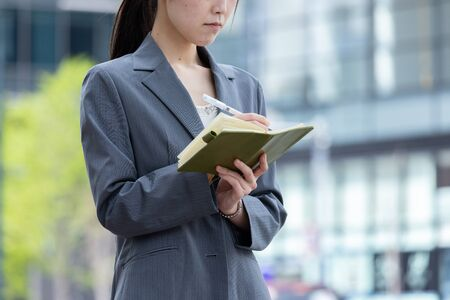 Young business woman checking notebook in office district Stok Fotoğraf