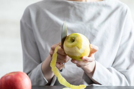 Young woman peeling an apple in the room
