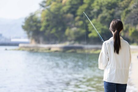 Young woman enjoying fishing at the seaside 写真素材