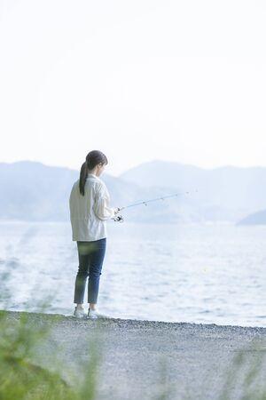 Young woman enjoying fishing at the seaside Foto de archivo