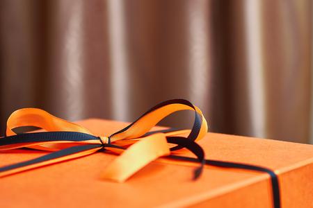 Élégant bel arc de rubans noirs et orange sur une boîte-cadeau orange. Banque d'images