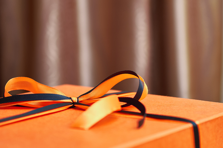 Stylish beautiful bow of black and orange ribbons on an orange gift box.