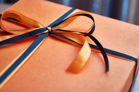 Beautiful bow of black and orange ribbons on an orange gift box. 스톡 콘텐츠