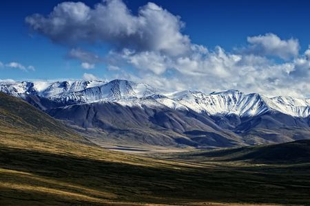 Beautiful colorful mountain landscape of snow-capped mountains under a bright sun and clouds.The play of light and shadow in a mountain valley.