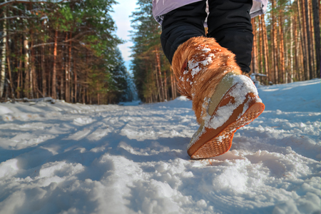 Leg woman in winter shoes walking on the snow in a winter park. Closeup outsole of warm boot.