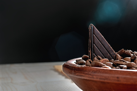 Piece of chocolate in fried coffee beans.  Rays of light. Stock Photo