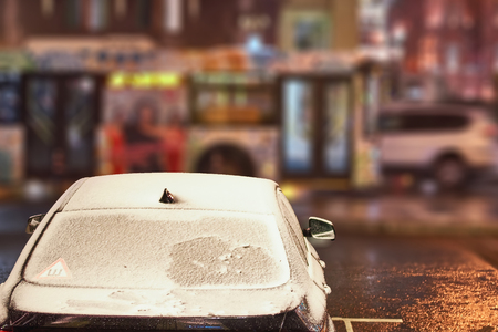 Car with the frozen windshield covered with ice and snow in a winter frosty night. Stock Photo