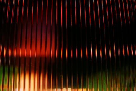 Multicolored abstract background blur of street lights. Multicolored striped lines and spots. View through the window of polycarbonate, Long exposure.