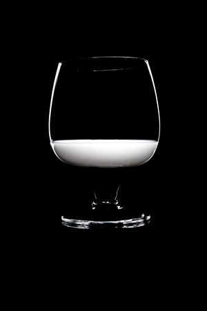 Glass with a white liqueur on a black background. For cutout. Stock Photo