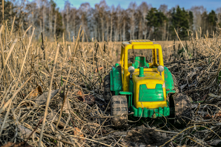 Closeup of a bright green and yellow tractor in the grass and straw. Childrens toys outdoors. Model of a car in the mud on the field. Selective focus. Stock Photo