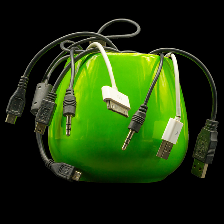 Wires for smartphones in a bright green cup on a black background for isolated. Abstract still-life Worm-eaten apple.Side view at eyes level.