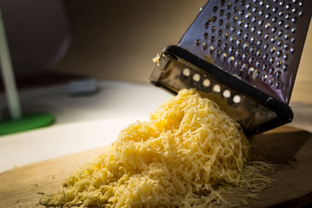 A pile of grated yellow fresh cheese on a wooden board against the background of a steel grater for cheese. Still life. Stock Photo