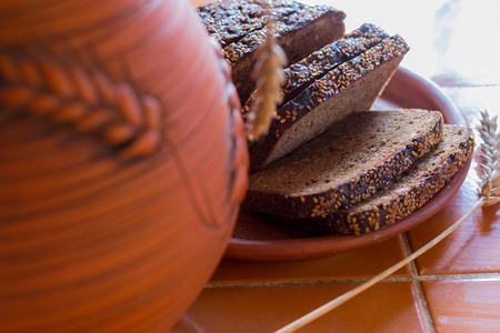 Sliced rye bread on a carved wooden board close-up. Against the background of pottery. Daylight. The kitchen table is covered with brown ceramic tiles.