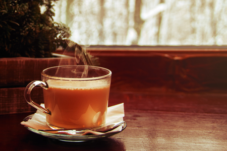 Cozy winter still life: cup of hot cocoa with steam, on wooden windowsill against snow landscape from outside. Winter background, copy space.