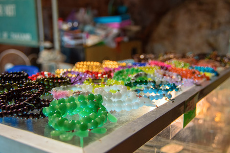 Souvenir glass beads of different colors lie on the counter. Concept of street trading the trinkets, cheap fakes