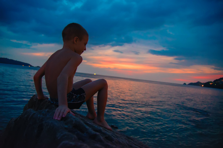 Side view portrait of a happy boy relaxing sitting on the rock and watching the sunset sea in the background. Copy space. Stock Photo