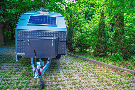 Solar panel is fixed on the tourist trailer. Off-road trailer stands in the parking lot on the background of thick green foliage. Copy space.