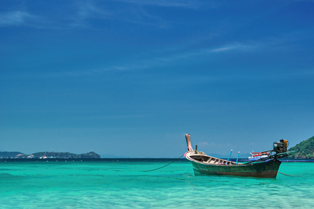 Fishing wooden boat at noon. Tropical sea in the background. Thailand. Panorama landscape. Clear turquoise water against a blue sky. Copy space.