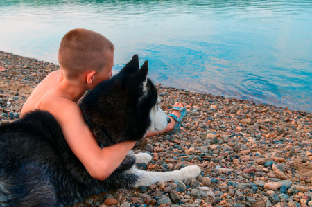 Cute boy hugged husky dog. Friends side by side sit on shore and look at the water. Summer evening. Rear view. Copy space. Foto de archivo