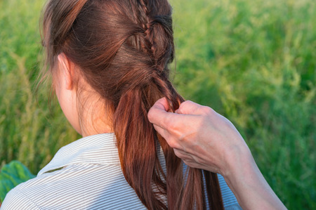 Back view long-haired girl with braid. Hands Female braiding daughter hair. Green grassy background. Copy space. Stock Photo