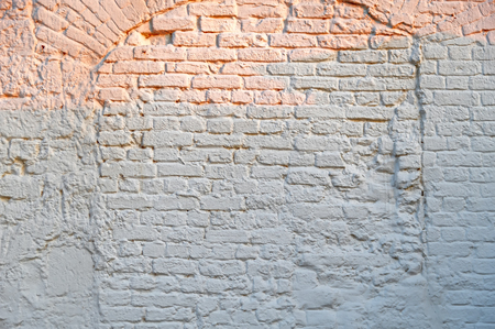 White Brick Wall Background with orange rays of the evening sun. Whitewash Brick Texture. White Brickwork Art Wallpaper. Old Lime Washed Wall Structure Stok Fotoğraf