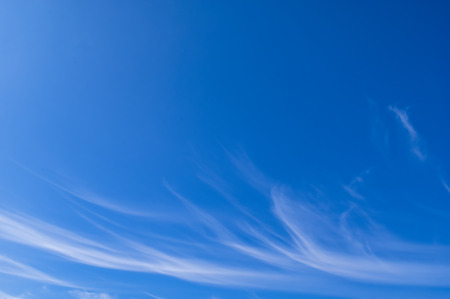 Light white cirrus clouds in the blue sky on a sunny day. Good weather in the morning