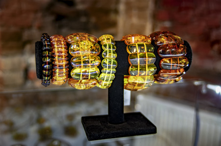 Amber jewelry bracelets on a black stand on the window of a jewelry store