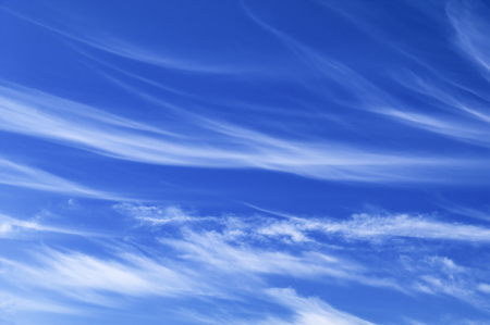 Light white cirrus clouds in the blue sky on a sunny day.