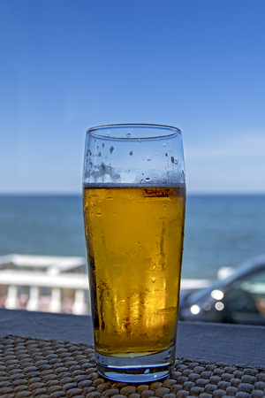 Misted glass of beer in the beach bar on the background of the sea landscape. Sunny day blue sky and sea. Stok Fotoğraf