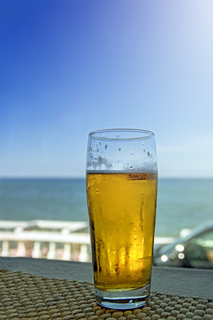 Misted glass of beer in the beach bar on the background of the sea landscape. Sunny hot day, afternoon