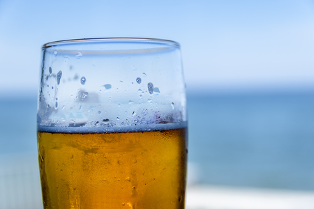 Misted glass of beer on the background of the sea landscape